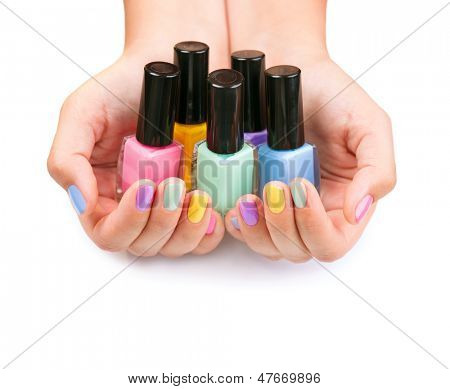 Nail Polish. Art Manicure. Multi-colored Nail Polish Bottles in the hands. Stylish Colorful Nails