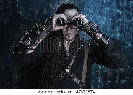 Portrait of a steampunk man looking through the binocular. Over dark grunge background.