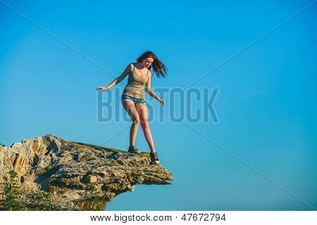 acrophobia woman tall stands on top of a rock cliff edge and is