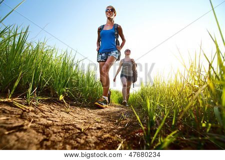 Two ladies hikers walking through green lush meadow