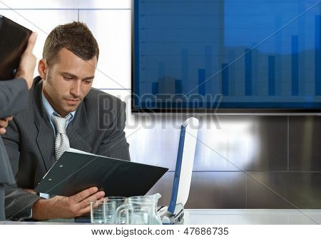 Young businessman sitting at meetingroom by table, looking at papers.