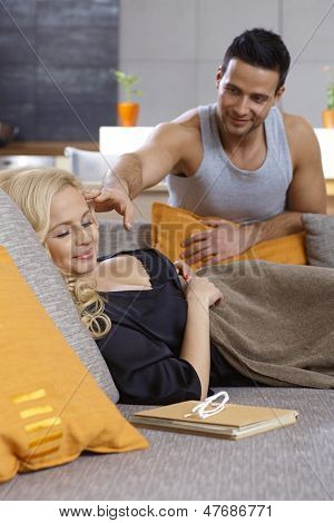 Young woman sleeping at home on sofa, man trying to wake her up, both smiling.