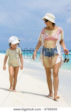 Daughter And Mother Walking On The Beach