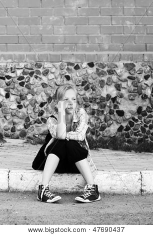 Sad young girl sitting on the sidewalk