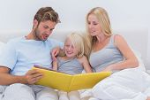 stock photo of short-story  - Couple reading a story to daughter in bed - JPG