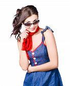 image of rockabilly  - Happy young pinup girl with smile wearing a red and blue rockabilly dress with neckerchief and style sunglasses studio portrait - JPG