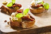 stock photo of baguette  - Italian cuisine appetizer bruschetta with tomatoes olives and cheese - JPG
