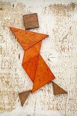 stock photo of tangram  - abstract figure of a female dancer built from seven tangram wooden pieces - JPG