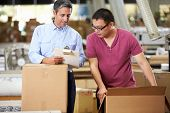 image of dispatch  - Workers In Warehouse Preparing Goods For Dispatch - JPG