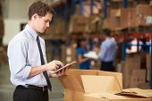 image of check  - Manager In Warehouse Checking Boxes Using Digital Tablet - JPG