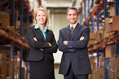 stock photo of dispatch  - Businesswoman And Businessman In Distribution Warehouse - JPG