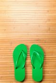 Green Flip Flops On Bamboo Mat With Copy Space