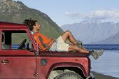foto of  jeep  - Side view of a mixed race man lying on hood of jeep near mountain lake - JPG