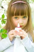 picture of rhinitis  - Little girl spraying medicine in nose nose drops nose spray - JPG