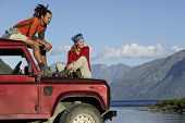 Man and woman sitting on top of jeep near mountain lake