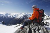 foto of wilder  - Side view of a male mountain climber using laptop on mountain peak - JPG