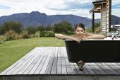 stock photo of bathtime  - Portrait of a beautiful woman in bathtub on porch against mountains - JPG