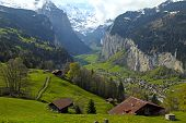 stock photo of chalet  - Beautiful traditional mountain village with waterfalls and snow peaks in the Alps - JPG