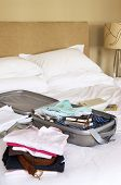 Closeup of stacks of folded clothes and packed suitcase on bed