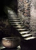 stock photo of staircases  - Spooky interior with ancient stone staircase and round vessel - JPG