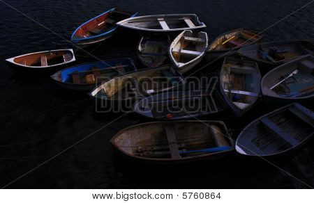 Old colored wooden rowing / fishing boats moored in a cove