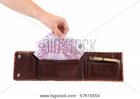 Hand holds euro bills in opened purse.