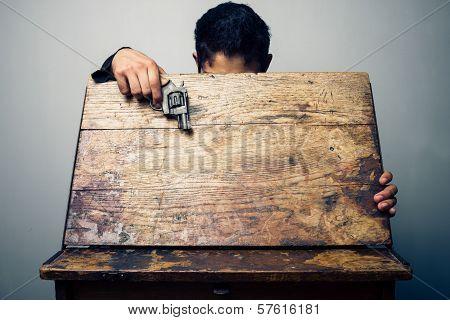 Student At School Desk With Gun