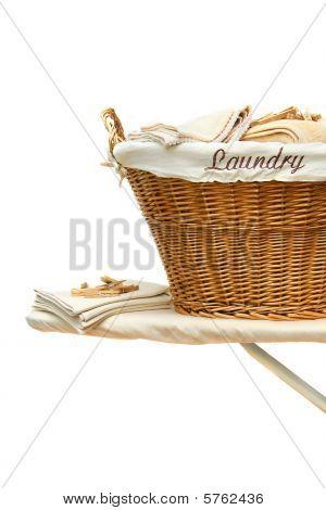 Cesta de lavanderia na tábua contra branco