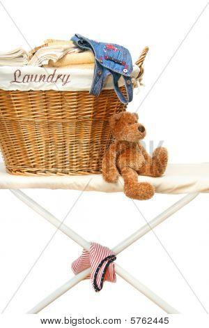 Urso de pelúcia com cesta de lavanderia na tábua