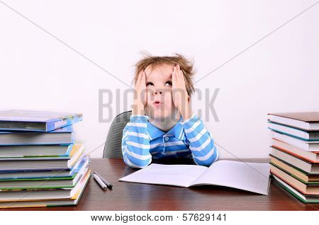 Boy Sitting At A Desk And Looking Up