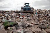 image of trash truck  - Garbage piles up in landfill site each day while truck covers it with sand for sanitary purpose - JPG