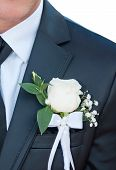 picture of boutonniere  - Groomsman in black wedding suit wearing rose boutonniere close - JPG