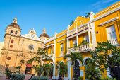 image of yellow castle  - Church and yellow colonial building visible from San Pedro Claver plaza in historic Cartagena Colombia - JPG