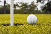 foto of caddy  - golf ball on lip of cup on grass