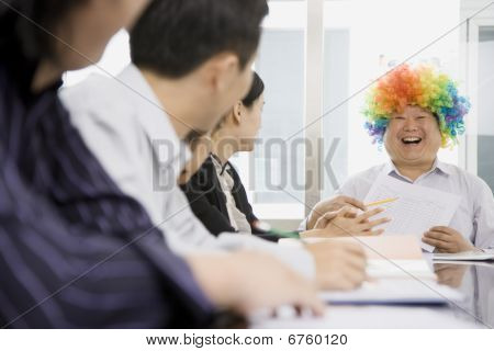 Businessman Wearing Clown Wig During Meeting