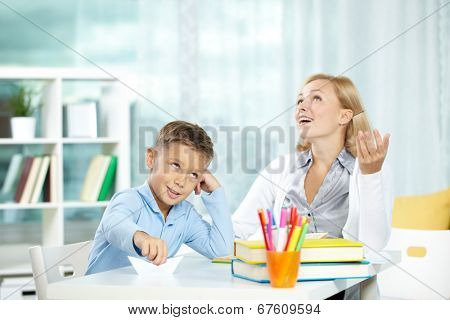 Portrait of handsome boy at workplace with his tutor sitting near by and telling something