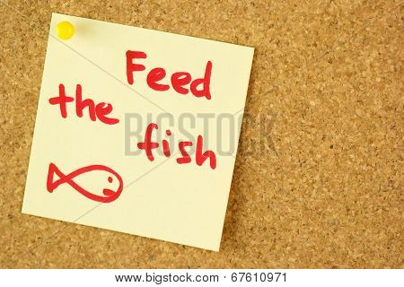 Feed the fish remind colorful yellow sticker pined  on corkboard