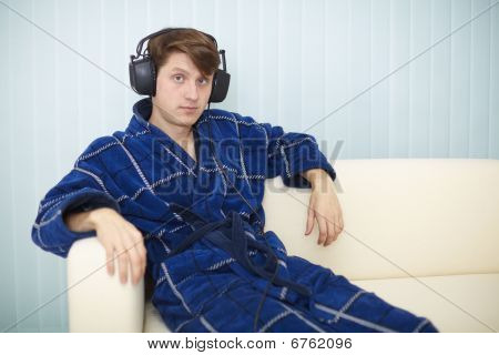 Man In Dark Blue Dressing Gown Listens To Music