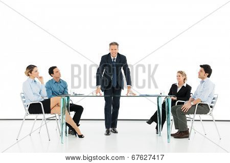 Portrait Of Mature Businessman With His Colleague In Business Meeting Against Projection Screen