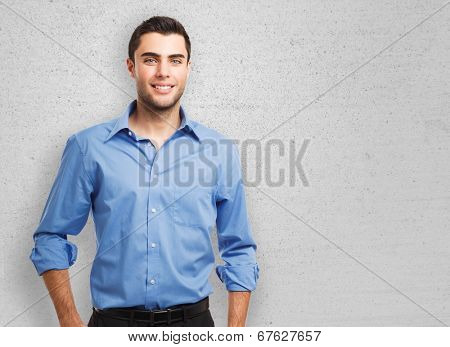 Portrait of an handsome young man leaning against a wall