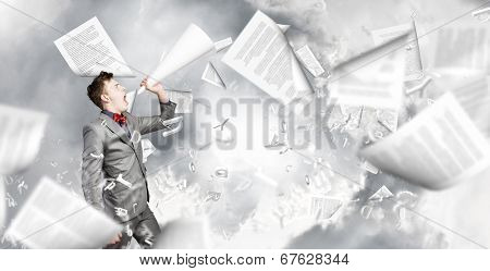 Young excited businessman screaming in paper trumpet