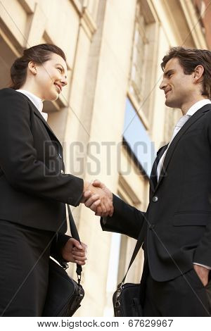 Businessman and business woman shaking hands outside building