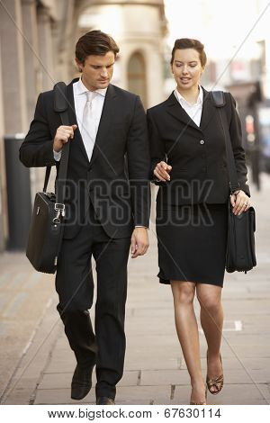 Businessman and businesswoman walking in street