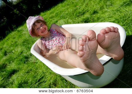 Girl In The Bath Outdoors On A Green Grass