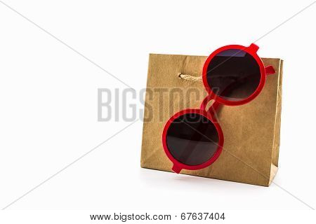 Stylish Red Glasses Hanging On Brown Shopping Bag.