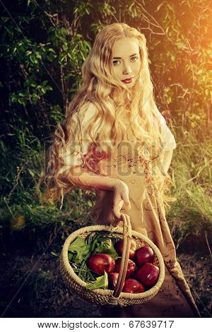 Beautiful young woman with magnificent blonde hair standing outdoor with a basket with apples. Countryside.