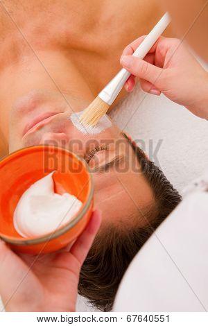 Therapist Applying Cream Man's Face