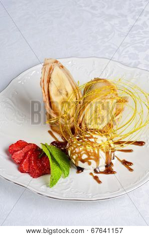 Dessert of pancake with banana, ice-cream, caramel, strawberry and mint