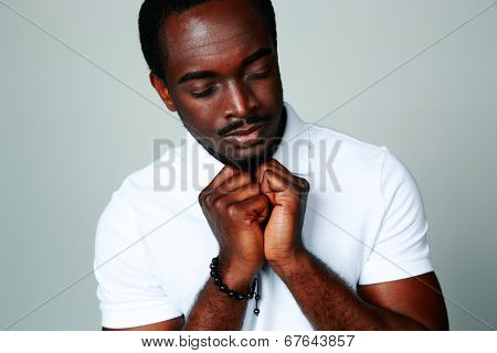 African man praying with his eyes closed on gray background