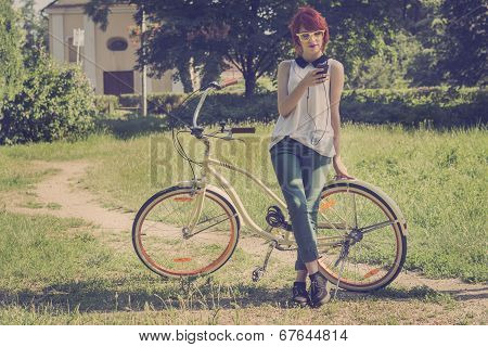 Hipster teenage girl on her vintage bike listening to the music